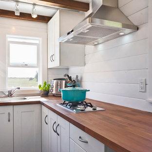 Modelo de cocina en L, costera, pequeña, sin isla, con fregadero encastrado, armarios con paneles lisos, puertas de armario blancas, encimera de madera, electrodomésticos de acero inoxidable y suelo de madera oscura