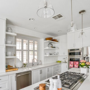 Mid-sized transitional kitchen inspiration - Mid-sized transitional l-shaped kitchen photo in Las Vegas with an undermount sink, shaker cabinets, white cabinets, white backsplash, subway tile backsplash, stainless steel appliances, an island and quartz countertops