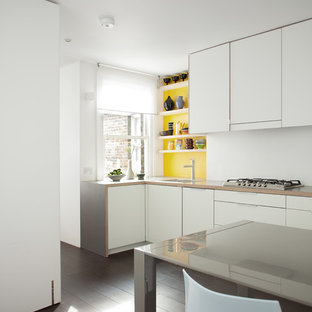 Medium sized contemporary l-shaped kitchen/diner in London with a single-bowl sink, flat-panel cabinets, white cabinets, laminate countertops, yellow splashback, stainless steel appliances, dark hardwood flooring and no island.