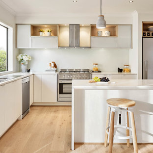 Inspiration for a contemporary l-shaped kitchen in Melbourne with a double-bowl sink, flat-panel cabinets, white cabinets, stainless steel appliances, light hardwood floors and an island.
