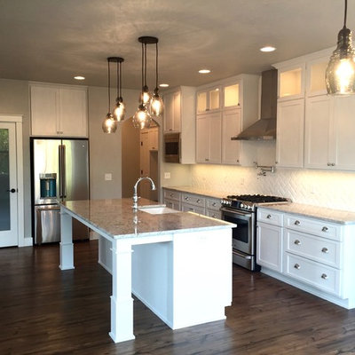 Eat-in kitchen - mid-sized craftsman l-shaped medium tone wood floor eat-in kitchen idea in Other with a farmhouse sink, shaker cabinets, white cabinets, granite countertops, white backsplash, ceramic backsplash, stainless steel appliances and an island