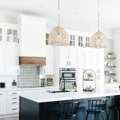 Example of a transitional galley light wood floor and beige floor kitchen design in Phoenix with an undermount sink, raised-panel cabinets, white cabinets, multicolored backsplash, stainless steel appliances, an island and white countertops