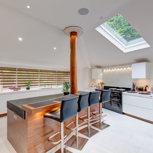 Photo of a medium sized contemporary kitchen in Cheshire with flat-panel cabinets, white splashback, travertine flooring, an island, white floors, a submerged sink, white cabinets and black appliances.
