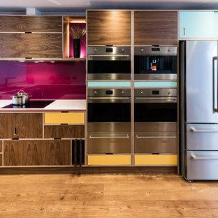 他の地域のミッドセンチュリースタイルのおしゃれなキッチン (フラットパネル扉のキャビネット、中間色木目調キャビネット、ピンクのキッチンパネル、シルバーの調理設備の、無垢フローリング、アイランドなし、茶色い床) の写真