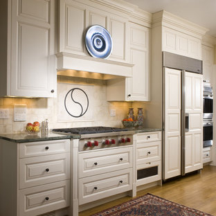 Traditional kitchen inspiration - Example of a classic kitchen design in Chicago with stainless steel appliances, white cabinets, granite countertops, beige backsplash and ceramic backsplash
