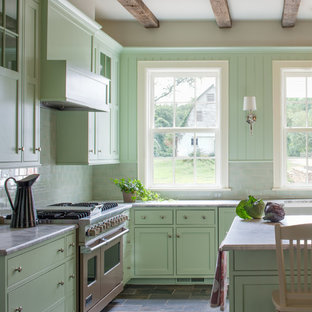This is an example of a country u-shaped eat-in kitchen in DC Metro with flat-panel cabinets, green cabinets, marble benchtops, green splashback, subway tile splashback, stainless steel appliances and slate floors.