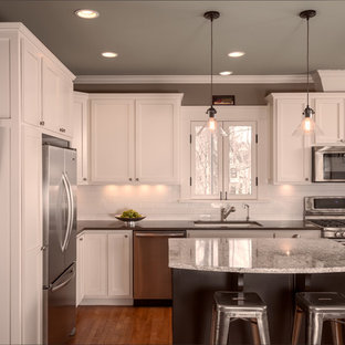 Traditional eat-in kitchen ideas - Example of a classic l-shaped light wood floor eat-in kitchen design in Nashville with an undermount sink, shaker cabinets, white cabinets, quartz countertops, white backsplash, subway tile backsplash, stainless steel appliances and an island