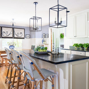 Mid-sized farmhouse eat-in kitchen inspiration - Eat-in kitchen - mid-sized farmhouse single-wall light wood floor eat-in kitchen idea in Boston with an undermount sink, white backsplash, porcelain backsplash, an island, raised-panel cabinets, white cabinets, granite countertops and stainless steel appliances