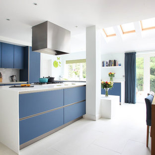 Inspiration for a modern kitchen/diner in London with flat-panel cabinets, blue cabinets, grey splashback and stainless steel appliances.