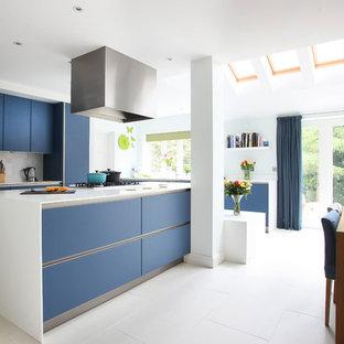 Aménagement d'une cuisine américaine moderne avec un placard à porte plane, des portes de placard bleues, une crédence grise et un électroménager en acier inoxydable.