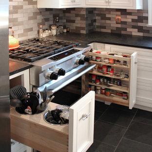 Immagine di una cucina chic di medie dimensioni con lavello stile country, ante con bugna sagomata, ante bianche, top in granito, paraspruzzi a effetto metallico, paraspruzzi con piastrelle di metallo, elettrodomestici in acciaio inossidabile, pavimento in ardesia e isola