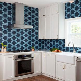 オースティンのトランジショナルスタイルのおしゃれなL型キッチン (エプロンフロントシンク、シェーカースタイル扉のキャビネット、白いキャビネット、青いキッチンパネル、シルバーの調理設備の、無垢フローリング) の写真