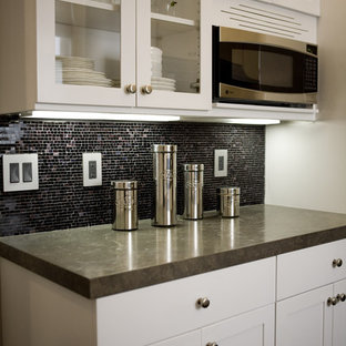 Design ideas for a contemporary kitchen in San Francisco with mosaic tile splashback, glass-front cabinets, white cabinets, black splashback, stainless steel appliances and limestone benchtops.