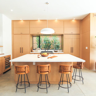 Contemporary kitchen inspiration - Kitchen - contemporary concrete floor and gray floor kitchen idea in Los Angeles with an undermount sink, flat-panel cabinets, light wood cabinets, window backsplash, paneled appliances and an island