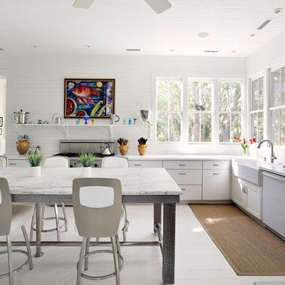 Eat-in kitchen - traditional l-shaped white floor eat-in kitchen idea in San Francisco with a farmhouse sink, flat-panel cabinets, white cabinets and stainless steel appliances