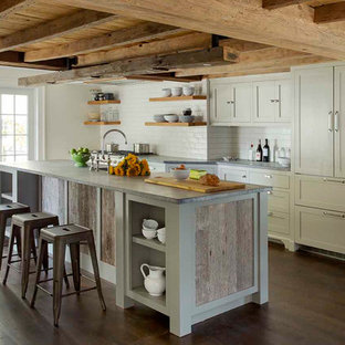 This is an example of a small country galley eat-in kitchen in Boston with a farmhouse sink, recessed-panel cabinets, grey cabinets, soapstone benchtops, white splashback, ceramic splashback, stainless steel appliances, dark hardwood floors and with island.