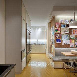 Foto på ett stort funkis kök och matrum, med släta luckor, vita skåp, vitt stänkskydd, rostfria vitvaror och gult golv