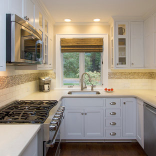 Photo of a small transitional u-shaped eat-in kitchen in Raleigh with an undermount sink, recessed-panel cabinets, white cabinets, quartz benchtops, white splashback, subway tile splashback, stainless steel appliances, dark hardwood floors, no island, brown floor and beige benchtop.