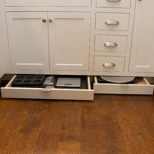 ローリーの小さいトランジショナルスタイルのおしゃれなキッチン (アンダーカウンターシンク、落し込みパネル扉のキャビネット、白いキャビネット、白いキッチンパネル、サブウェイタイルのキッチンパネル、シルバーの調理設備、クオーツストーンカウンター、濃色無垢フローリング、アイランドなし、茶色い床、ベージュのキッチンカウンター) の写真