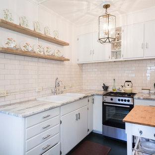 シカゴの小さいエクレクティックスタイルのおしゃれなキッチン (ドロップインシンク、フラットパネル扉のキャビネット、白いキャビネット、珪岩カウンター、白いキッチンパネル、セラミックタイルのキッチンパネル、シルバーの調理設備の、コルクフローリング、黒い床) の写真