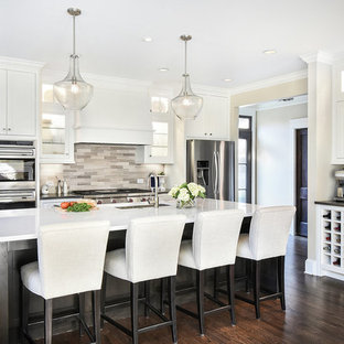 Large transitional kitchen photos - Large transitional dark wood floor kitchen photo in Atlanta with an undermount sink, white cabinets, quartz countertops, stainless steel appliances, an island, glass-front cabinets, multicolored backsplash and limestone backsplash