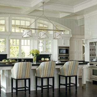 Idéer för ett mycket stort klassiskt svart kök och matrum, med luckor med infälld panel, vita skåp, granitbänkskiva, rostfria vitvaror, en köksö, vitt stänkskydd och stänkskydd i tunnelbanekakel