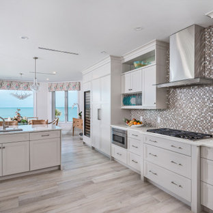 Large coastal eat-in kitchen remodeling - Example of a large beach style l-shaped porcelain tile and beige floor eat-in kitchen design in Miami with an undermount sink, recessed-panel cabinets, quartzite countertops, multicolored backsplash, glass tile backsplash, paneled appliances, an island, white countertops and gray cabinets