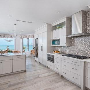Große Maritime Wohnküche in L-Form mit Unterbauwaschbecken, Schrankfronten mit vertiefter Füllung, Quarzit-Arbeitsplatte, bunter Rückwand, Rückwand aus Glasfliesen, Elektrogeräten mit Frontblende, Porzellan-Bodenfliesen, Kücheninsel, beigem Boden, weißer Arbeitsplatte und grauen Schränken in Miami