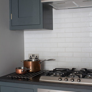 This is an example of a small contemporary l-shaped enclosed kitchen in Other with a submerged sink, shaker cabinets, granite worktops, white splashback, stainless steel appliances, medium hardwood flooring, no island, grey cabinets and metro tiled splashback.