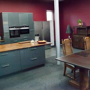 他の地域の大きいモダンスタイルのおしゃれなキッチン (フラットパネル扉のキャビネット、黒いキャビネット、木材カウンター、黒い床) の写真