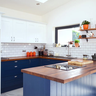 This is an example of a medium sized traditional u-shaped kitchen/diner in Edinburgh with shaker cabinets, blue cabinets, wood worktops, a breakfast bar, a built-in sink, white splashback, metro tiled splashback and white floors.