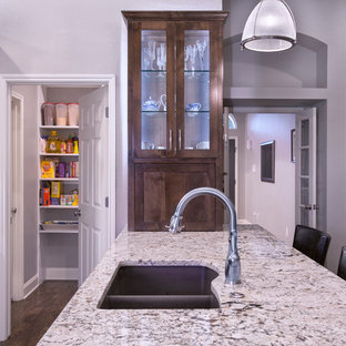 Medium sized contemporary u-shaped kitchen pantry in Dallas with a double-bowl sink, shaker cabinets, white cabinets, granite worktops, beige splashback, mosaic tiled splashback, stainless steel appliances, vinyl flooring, a breakfast bar and brown floors.