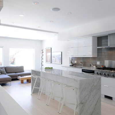Example of a mid-sized danish single-wall light wood floor eat-in kitchen design in Ottawa with an undermount sink, flat-panel cabinets, white cabinets, marble countertops, gray backsplash, porcelain backsplash, stainless steel appliances and an island