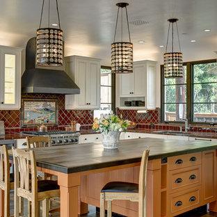 サンタバーバラの大きい地中海スタイルのおしゃれなキッチン (アンダーカウンターシンク、白いキャビネット、赤いキッチンパネル、セラミックタイルのキッチンパネル、シルバーの調理設備の、無垢フローリング、タイルカウンター、落し込みパネル扉のキャビネット、赤いキッチンカウンター) の写真
