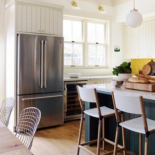 Design ideas for a large country l-shaped eat-in kitchen in San Francisco with a farmhouse sink, flat-panel cabinets, beige cabinets, quartzite benchtops, yellow splashback, terra-cotta splashback, stainless steel appliances, medium hardwood floors, with island and white benchtop.