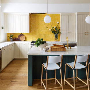 Large transitional l-shaped eat-in kitchen in San Francisco with a farmhouse sink, flat-panel cabinets, beige cabinets, quartzite benchtops, yellow splashback, terra-cotta splashback, stainless steel appliances, medium hardwood floors, with island, white benchtop and brown floor.