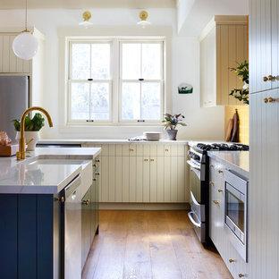 Inspiration för ett stort lantligt vit vitt kök, med en rustik diskho, släta luckor, beige skåp, bänkskiva i kvartsit, gult stänkskydd, stänkskydd i terrakottakakel, rostfria vitvaror, mellanmörkt trägolv och en köksö