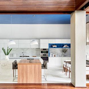 シャーロットの大きいモダンスタイルのおしゃれなキッチン (アンダーカウンターシンク、フラットパネル扉のキャビネット、白いキャビネット、大理石カウンター、白いキッチンパネル、大理石の床、パネルと同色の調理設備、大理石の床、白い床、白いキッチンカウンター) の写真
