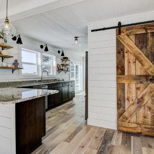 Ejemplo de cocina comedor en L, de estilo de casa de campo, con fregadero bajoencimera, armarios estilo shaker, puertas de armario de madera en tonos medios, encimera de granito, suelo de madera clara y suelo multicolor