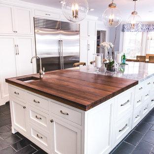 Lantlig inredning av ett stort kök, med en undermonterad diskho, luckor med infälld panel, vita skåp, bänkskiva i kvarts, rostfria vitvaror, skiffergolv, en köksö, svart golv, grått stänkskydd och stänkskydd i marmor