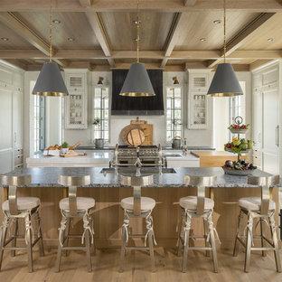 Immagine di una cucina tradizionale con lavello sottopiano, ante con riquadro incassato, ante bianche, paraspruzzi bianco, elettrodomestici in acciaio inossidabile, parquet chiaro e 2 o più isole
