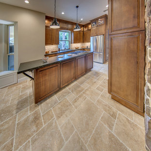 This is an example of a medium sized classic u-shaped kitchen in Houston with a submerged sink, raised-panel cabinets, medium wood cabinets, soapstone worktops, beige splashback, stone tiled splashback, stainless steel appliances, travertine flooring, an island and beige floors.