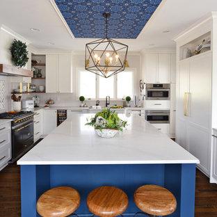 Diseño de cocina tradicional renovada con armarios estilo shaker, puertas de armario blancas, salpicadero verde, electrodomésticos de acero inoxidable, suelo de madera oscura, una isla, suelo marrón y encimeras grises
