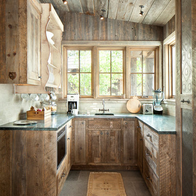 Inspiration for a small rustic u-shaped cement tile floor kitchen remodel in Orange County with an undermount sink, flat-panel cabinets, distressed cabinets, solid surface countertops, white backsplash, ceramic backsplash and no island