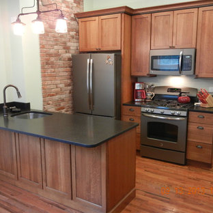 Traditional kitchen ideas - Example of a classic medium tone wood floor kitchen design in Burlington with medium tone wood cabinets and an island