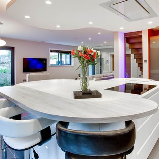 他の地域の広いモダンスタイルのおしゃれなキッチン (ドロップインシンク、フラットパネル扉のキャビネット、グレーのキャビネット、珪岩カウンター、白いキッチンパネル、レンガのキッチンパネル、シルバーの調理設備、セラミックタイルの床) の写真