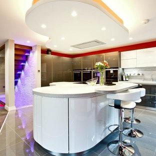他の地域の大きいモダンスタイルのおしゃれなキッチン (ドロップインシンク、フラットパネル扉のキャビネット、グレーのキャビネット、珪岩カウンター、白いキッチンパネル、レンガのキッチンパネル、シルバーの調理設備の、セラミックタイルの床) の写真