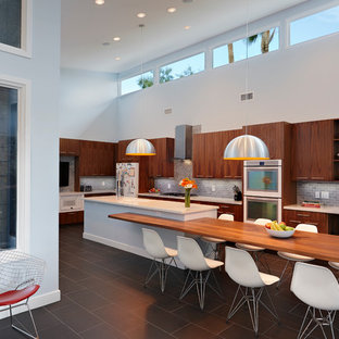 Large midcentury modern kitchen designs - Large 1960s l-shaped kitchen photo in Las Vegas with flat-panel cabinets, medium tone wood cabinets, gray backsplash and an island