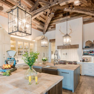 Inspiration for an expansive country u-shaped eat-in kitchen in Austin with a farmhouse sink, shaker cabinets, beige cabinets, beige splashback, panelled appliances, light hardwood floors, multiple islands, white benchtop, marble benchtops and terra-cotta splashback.