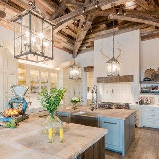 オースティンの巨大なカントリー風おしゃれなキッチン (エプロンフロントシンク、シェーカースタイル扉のキャビネット、ベージュのキャビネット、ベージュキッチンパネル、パネルと同色の調理設備、淡色無垢フローリング、白いキッチンカウンター、大理石カウンター、テラコッタタイルのキッチンパネル) の写真